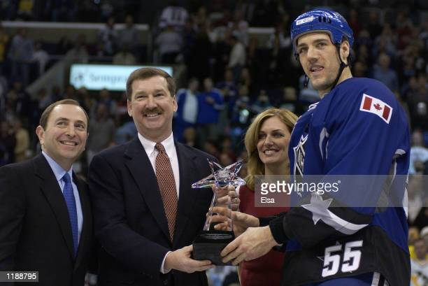 Eric Daze of the North America AllStars accepts his MVP Award from NHL Commissioner Gary Bettman Senior Brand Manager of Bud Light Phil Ware and...