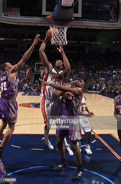 Erick Dampier of the Golden State Warriors shoots over Alton Ford of the Phoenix Suns at The Arena in Oakland California DIGITAL IMAGE NOTE TO USER...