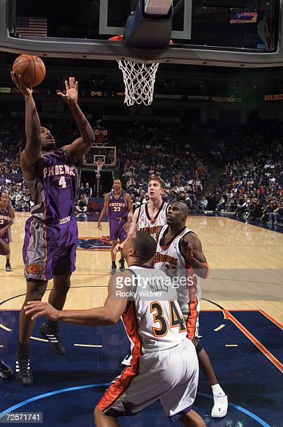 Forward Alton Ford of the Phoenix Suns shoots over forward Chris Mills of the Golden State Warriors during the NBA game at the Arena in Oakland in...
