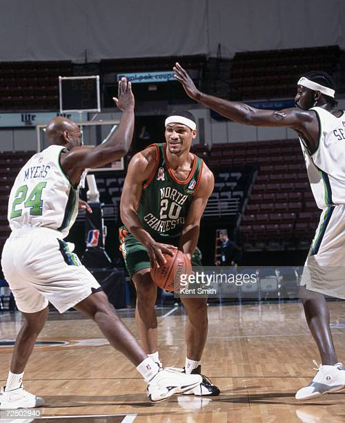 Forward Antonio Grant of the North Charleston Lowgators prepares to shoot the ball as two Greenville Groove - guard Jeff Myers and forward Ansu Sesay...