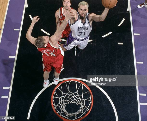 Forward Scot Pollard of the Sacramento Kings shoots over forward Hanno Mottola of the Atlanta Hawks during the NBA game at Arco Arena in Sacramento...