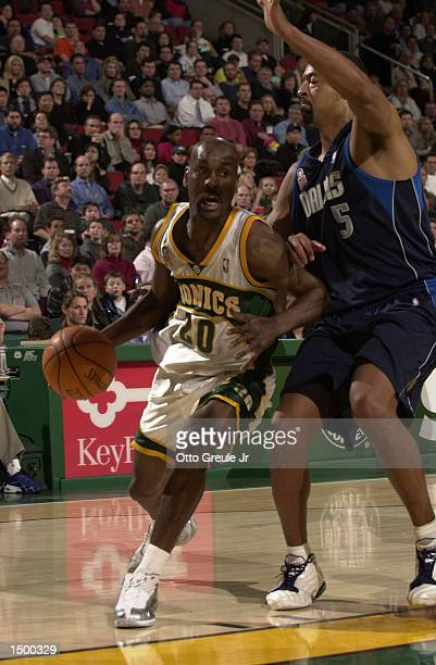 Gary Payton of the Seattle Supersonics drives against Juwan Howard of the Dallas Mavericks at Key Arena in Seattle Washington The Mavericks defeated...