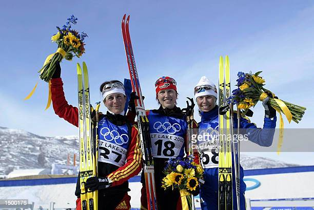 Gold medal winner Kati Wilhelm of Germany silver medal winner Uschi Disl of Germany and Magdalena Forsberg of Sweden celebrate after the women's 75km...