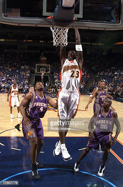Guard Jason Richardson of the Golden State Warriors dunks over forward Alton Ford of the Phoenix Suns during the NBA game at the Arena in Oakland in...