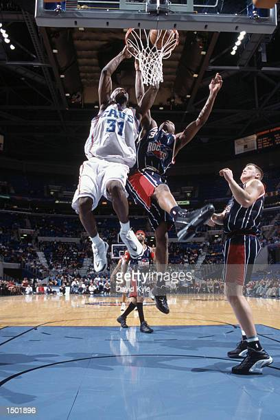 Guard Ricky Davis of the Cleveland Cavaliers dunks over guard Steve Francis of the Houston Rockets during the NBA game at Gund Arena in Cleveland...