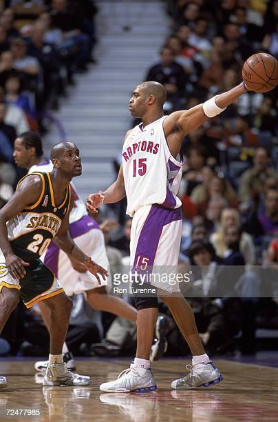 Guard Vince Carter of the Toronto Raptors holds the ball as guard Gary Payton of the Seattle SuperSonics plays defense during the NBA game at Air...