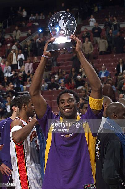 Kobe Bryant of the Los Angeles Lakers hoists his MVP trophy after the 2002 NBA All-Star game at the First Union Center during the 2002 NBA All-Star...