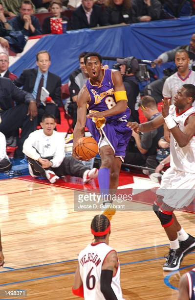 Kobe Bryant of the Western Conference team and the Los Angeles Lakers looks to pass around Dikembe Mutombo of the Eastern Conference team and the...