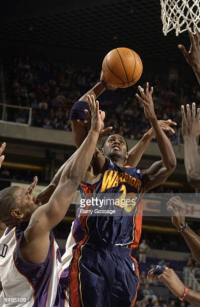 Larry Hughes of the Golden State Warriors shoots against Alton Ford of the Phoenix Suns during an NBA game at America West Arena in Phoenix Arizona...