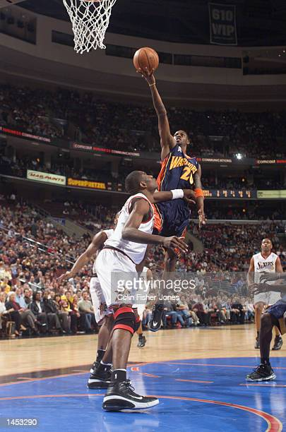 Larry Hughes of the Golden State Warriors with the finger role over Dikembe Mutombo of the Philadelphia 76ers at the First Union Center in...