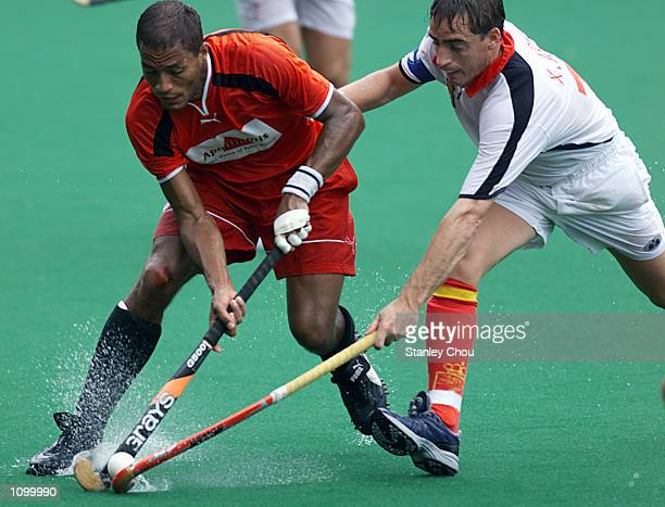 Michael Green of Germany is checked by Xavier Arnau of Spain during the World Cup Hockey match between Germany and Spain held at the Bukit Jalil...