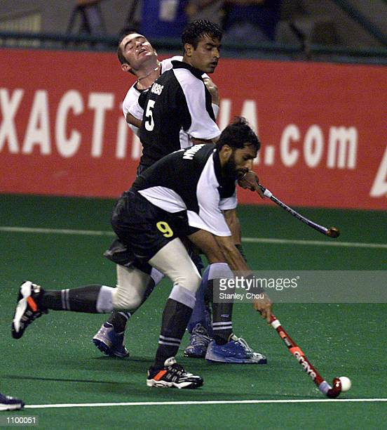 Muhammad Usman of Pakistan takes the ball away as Teammate Sohail Abbas held out Phillips Burrows of New Zealand during the World Cup Hockey match...