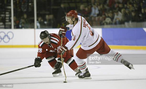 Oleg Romanov of Belarus tries to send the puck forward in front of Martin Pluss of Switzerland during the third period in the men's hockey...