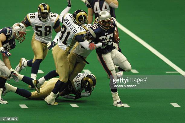 Patrick Pass of the New England Patriots is pressured by Adam Archuleta and Robert Holcombe of the StLouis Rams during Superbowl XXXVI at the...