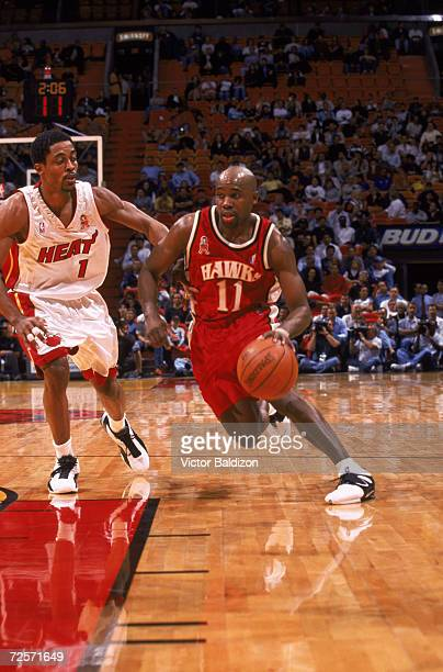 Point guard Jacque Vaughn of the Atlanta Hawks drives past point guard Rod Strickland of the Miami Heat during the NBA game at American Airlines...