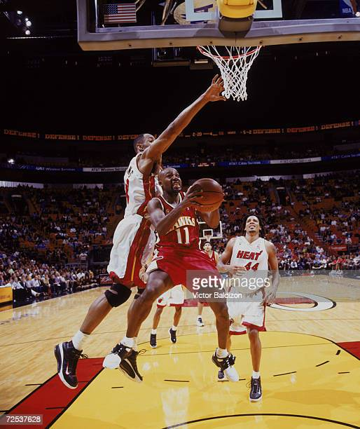 Point guard Jacque Vaughn of the Atlanta Hawks shoots past center Alonzo Mourning of the Miami Heat during the NBA game at American Airlines Arena in...