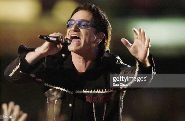 Singer Bono of the band U2 performs during the halftime show of Superbowl XXXVI at the Superdome in New Orleans Louisiana The New England Patriots...