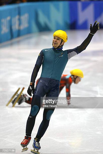 Steven Bradbury of Australia celebrates winning the gold medal after crossing the finish line as Mathieu Turcott of Canada lies on the ice behind him...