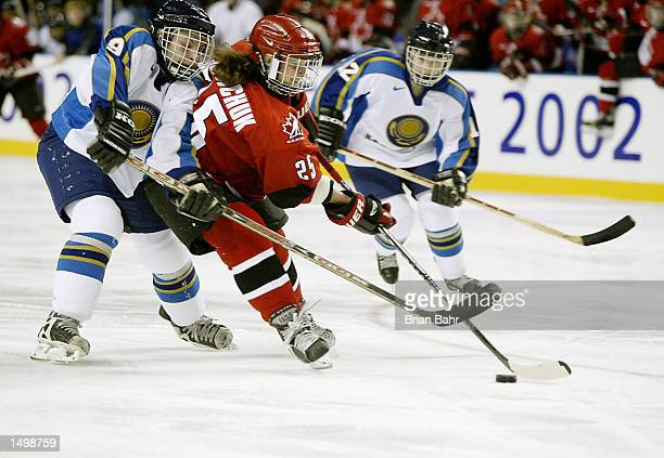 Tammy Lee Shewchuk of Canada breaks away for a goal despite being caught by Olga Potapova of Kazakhstan in the second period during their preliminary...