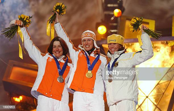 Uschi Disl of Germany silver Kati Wilhelm of Germany gold Magdalena Forsberg of Sweden bronze receive their medals in the women's biathlon 75km...