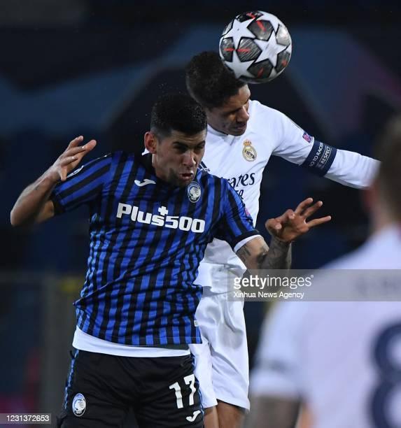 Feb. 24, 2021 -- Real Madrid's Raphael Varane R vies with Atalanta's Cristian Romero during a UEFA Champions League round of 16 first leg football...
