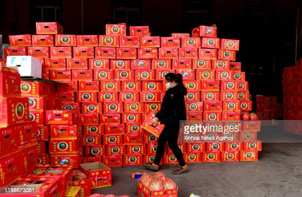 Feb. 4, 2020 -- A woman arranges boxes of fruits at Wanbang wholesale market of agricultural products in Zhongmu County of Zhengzhou, central China's...