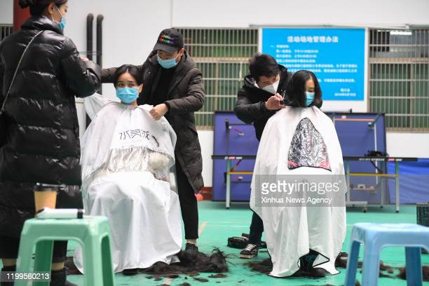 Feb. 8, 2020 -- Medical team members have their hair cut to better wear protective products before leaving for Wuhan of Hubei Province, at the Third...