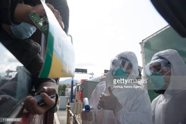 WENZHOU Feb 8 2020 Pakistani Abdul Zahir Hamad R and his wife Mauritian Hosany Sumayyah check the car information at a novel coronavirus...