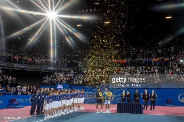 MONTPELLIER FRANCE February 10 JoWilfried Tsonga of France with the winners trophy after his victory against PierreHughes Herbert of France who holds...