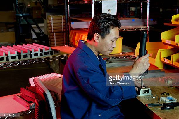 GOLDEN COLO February 13 2004 Thong Sajopha <cq> a technician at Epilog Laser in Golden assembles components for one of the company's CO2 laser...
