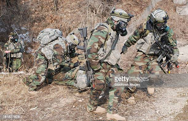 February 14, 2012 - U.S. Soldiers wear gas masks as they extract a soldier during force-on-force training at the live-fire complex on Camp Rodriguez, Republic of Korea.