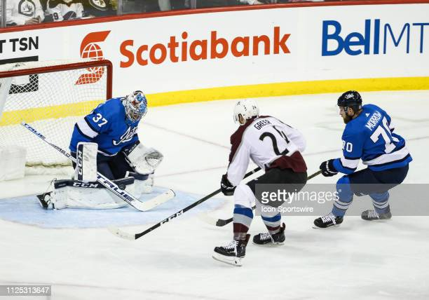 Winnipeg Jets goalie Connor Hellebuyck makes a save on Colorado Avalanche forward AJ Greer during the regular season game between the Winnipeg Jets...