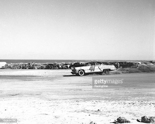 Curtis Turner kicks up some sand leaving the south turn of the Daytona BeachRoad Course on his way to finishing seventh in the NASCAR Cup race Turner...