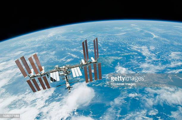 february 19, 2010 - the international space station backdropped by earth's horizon and the blackness of space. - international space station fotografías e imágenes de stock