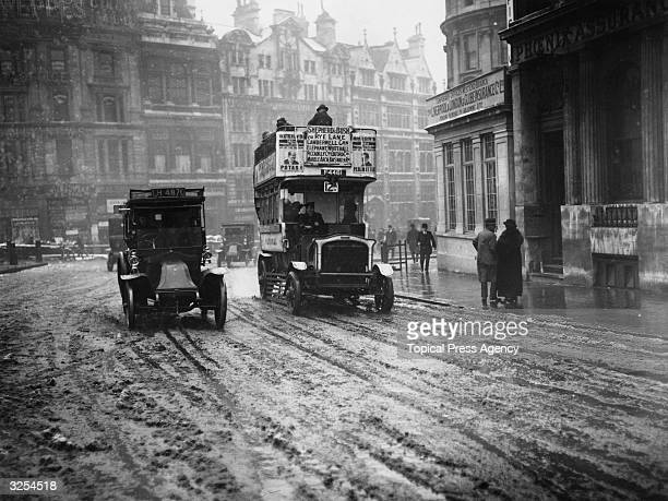 A taxi and a bus in the snow at Trafalgar Square in London