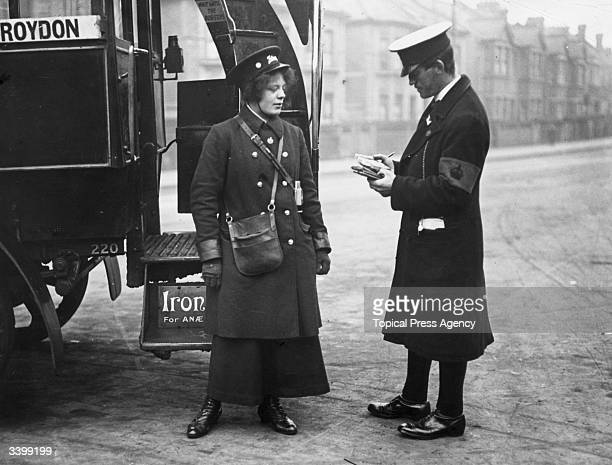 A regulator taking the time of London bus journeys from a new woman bus conductor during the First World War