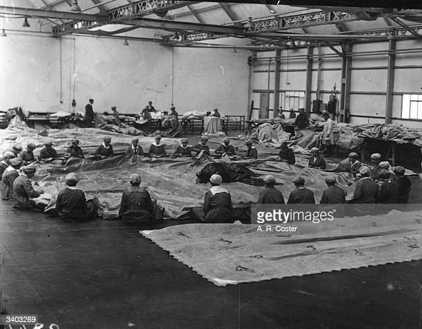 Factory workers sewing the outer cover for a Zepplin airship at the Zeppelin building at Short Bros