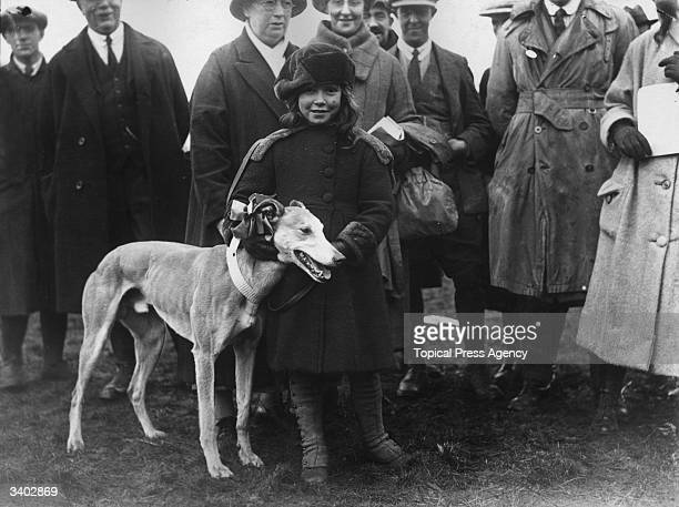 A young girl holds a greyhound 'Jassiona' which is wearing a large rosette and is running in the Waterloo Plate during the Waterloo Cup Meeting held...