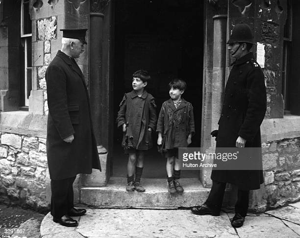 Two boys are asked by policemen if they would like new clothes and shoes from the Plymouth Police Clothing Fund