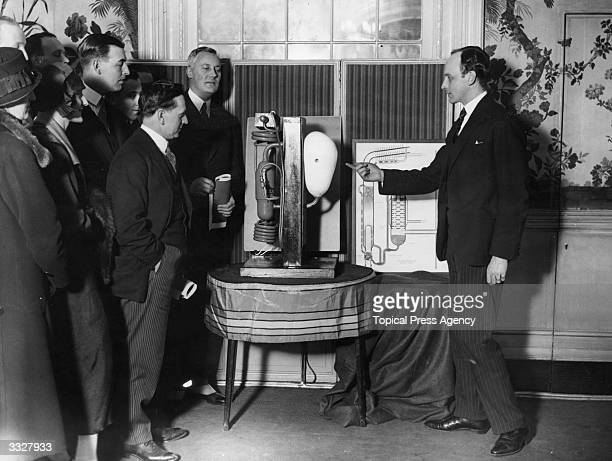 An 'Electrolux' representative demonstrates the mechanics of one of the company's refrigerators to a group of people at the Savoy Hotel in London