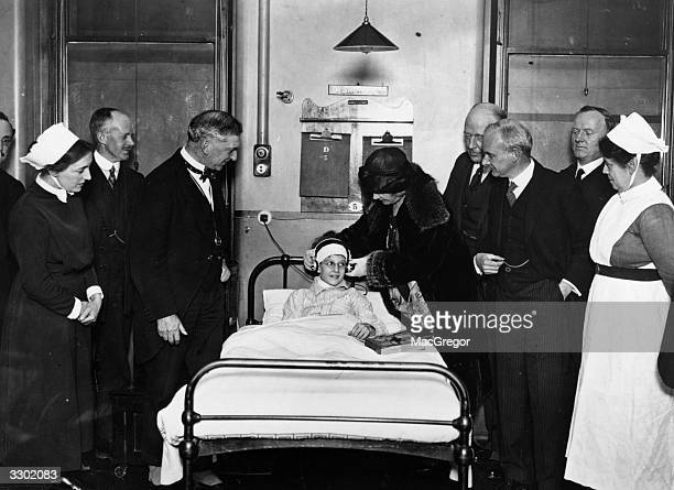 Lady Simson places new headphones on a young patient's head during the presentation of a wireless set by the Daily News to the West London Hospital...