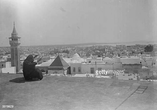 Man on a rooftop raise his arms as he faces the city of Tunis spread out before him.