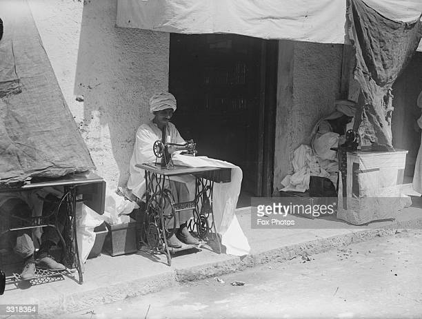 Shaded from the sun turbanned men sit at Singer sewing machines lining the street