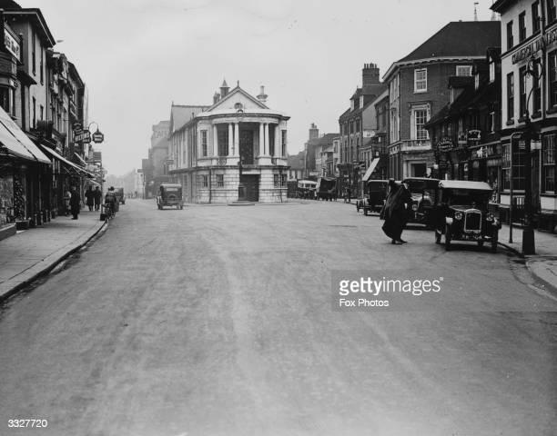 A car travels along Ashford High Street the main throughfare of Ashford Kent