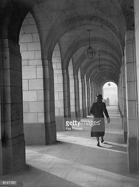 Woman walks down a covered archway at Shell Mex House, London.