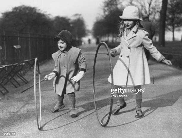Two girls rolling hoops with sticks in Hyde park in London
