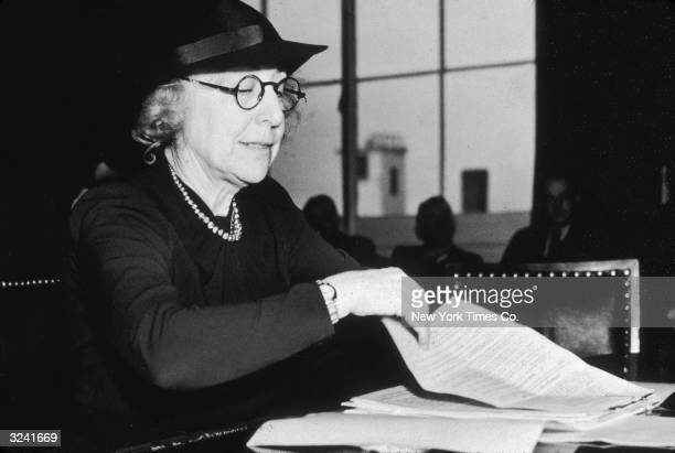 Jeannette Rankin legislative secretary of the National Council for Prevention of War leafs through papers as she testifies before the House Naval...