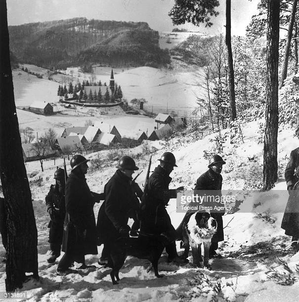 A French patrol with a Saint Bernard make their way through a beautiful snowy valley in France during World War II