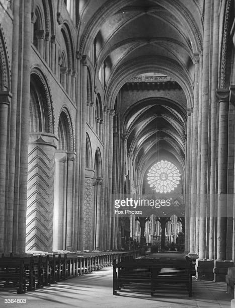 The interior of Durham Cathedral, looking through the nave towards the altar and stained glass window. This massive Anglo-Norman construction was...