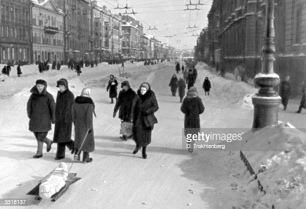 A woman carries away a corpse on a sledge down Nevski Prospect Leningrad's main avenue during the siege of Leningrad when many died of starvation